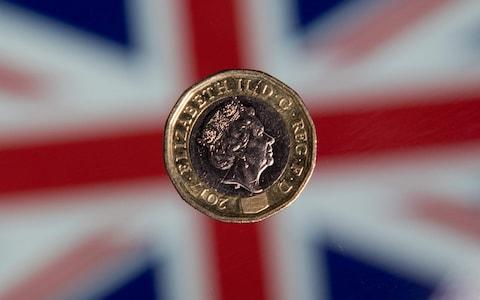 British one pound sterling coin is arranged for a photograph in front of a Union flag - Credit: JUSTIN TALLIS/AFP
