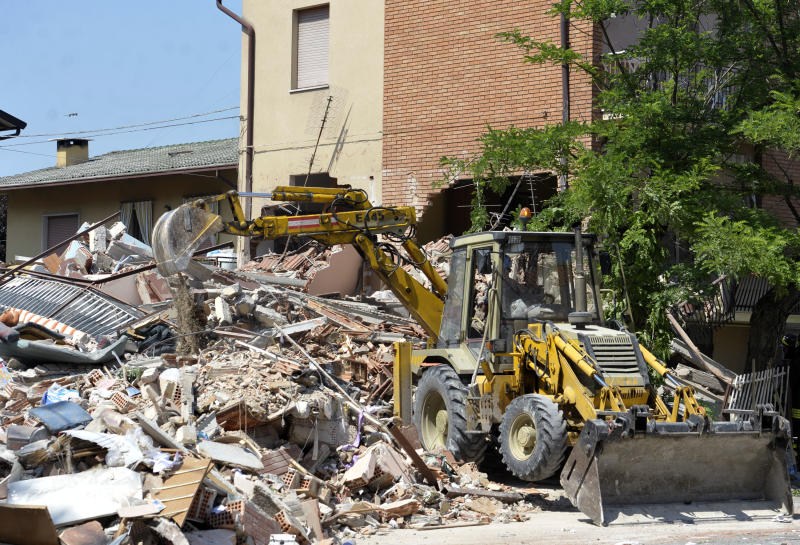 An excavator removes debris in Cavezzo, northern Italy, Tuesday, May 29, 2012. A powerful earthquake killed at least 15 people Tuesday as it rocked a swath of northern Italy. Factories, warehouses and churches collapsed, dealing another blow to a region where thousands are still homeless from a stronger temblor just nine days ago. The 5.8 magnitude quake drove thousands more from their homes in the Emilia Romagna region north of Bologna, one of Italy's most agriculturally and industrial productive areas. (AP Photo/Marco Vasini)