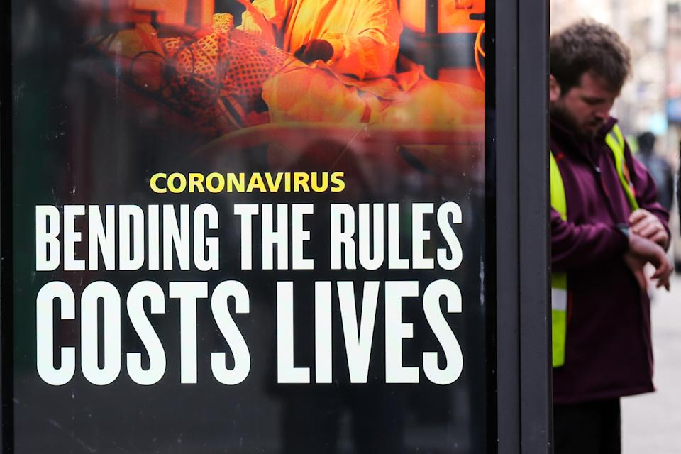 LONDON, UNITED KINGDOM - 2021/01/22: A man looks at his watch while standing next to a covid-19 prevention publicity campaign poster in London. According to the Office for National Statistics (ONS) as of January 15 there had been over 103,000 Covid-19 deaths in the UK. (Photo by Dinendra Haria/SOPA Images/LightRocket via Getty Images)
