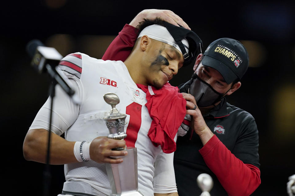 Ohio State head coach Ryan Day hugs quarterback Justin Fields.