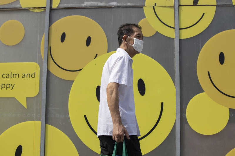A resident wearing a mask to curb the spread of the coronavirus walks past smiley faces outside a mall in Beijing Thursday, July 16, 2020. China's economy rebounded from a painful contraction to grow by 3.2% over a year earlier in the latest quarter as anti-virus lockdowns were lifted and factories and stores reopened (AP Photo/Ng Han Guan)