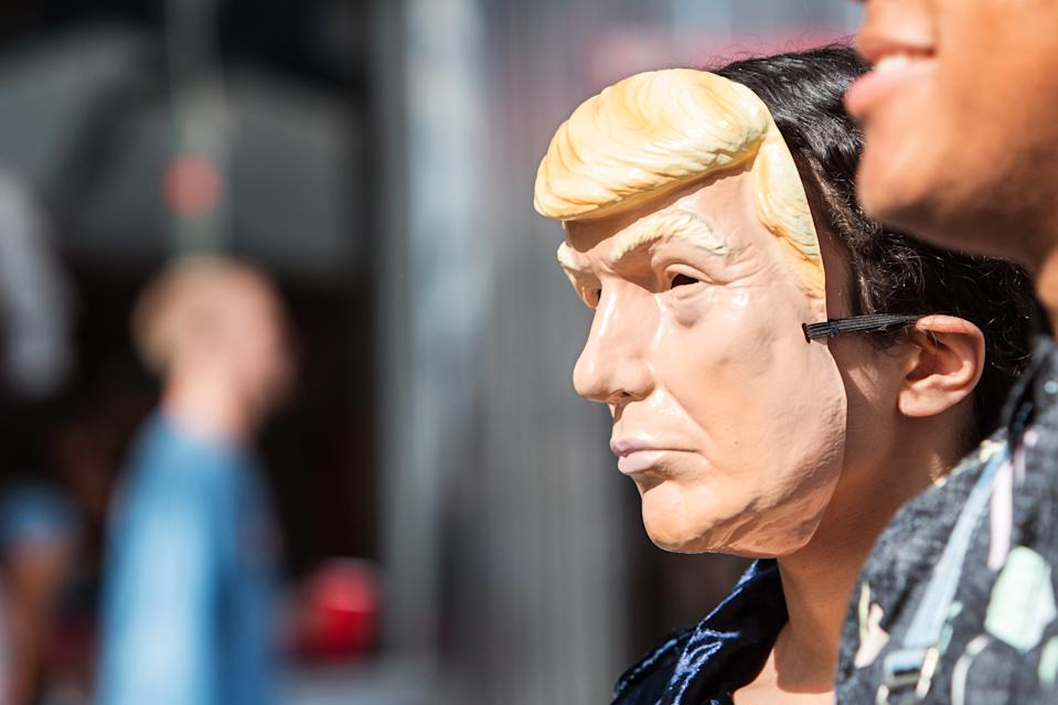 A person wears a Donald Trump mask at the Little Five Points Halloween Parade on October 21, 2017 in Atlanta, GA.