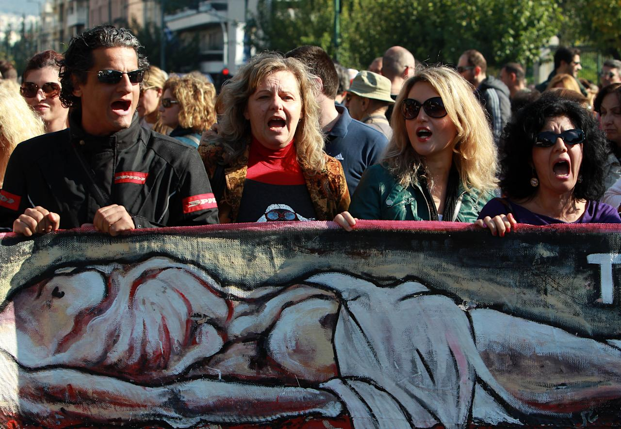 Protesting civil servants carrying a banner showing an image of an emaciated body shout slogans during a  rally outside the Public Sector Reform ministry in Athens on Tuesday, Nov. 13, 2012. Civil servants face a new round of pay cuts under austerity measures approved by parliament last week. Despite concerns over Greece's long-term economic outlook, the country's euro partners and the International Monetary Fund are expected to agree on the release of the next tranche of the bailout over the next week. (AP Photo/Thanassis Stavrakis)