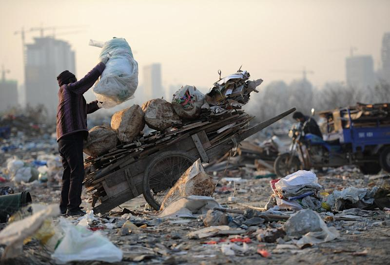 A woman collects construction waste in a rubbish dump in Hefei, central China's Anhui province in December 2012