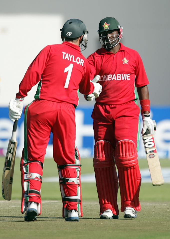 Zimbabwe batsman Hamilton Masakadza (R) is congratulated by captain Brendan Taylor (L) on reaching 50 runs during the first game of the three match ODI cricket series between Pakistan and hosts Zimbabwe at the Harare Sports Club on August 27, 2013.AFP PHOTO / JEKESAI NJIKIZANA        (Photo credit should read JEKESAI NJIKIZANA/AFP/Getty Images)