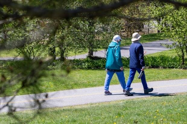 Two people wearing masks walk along a path in Britannia Park on a sunny spring day on May 12, 2021. (Francis Ferland/CBC - image credit)
