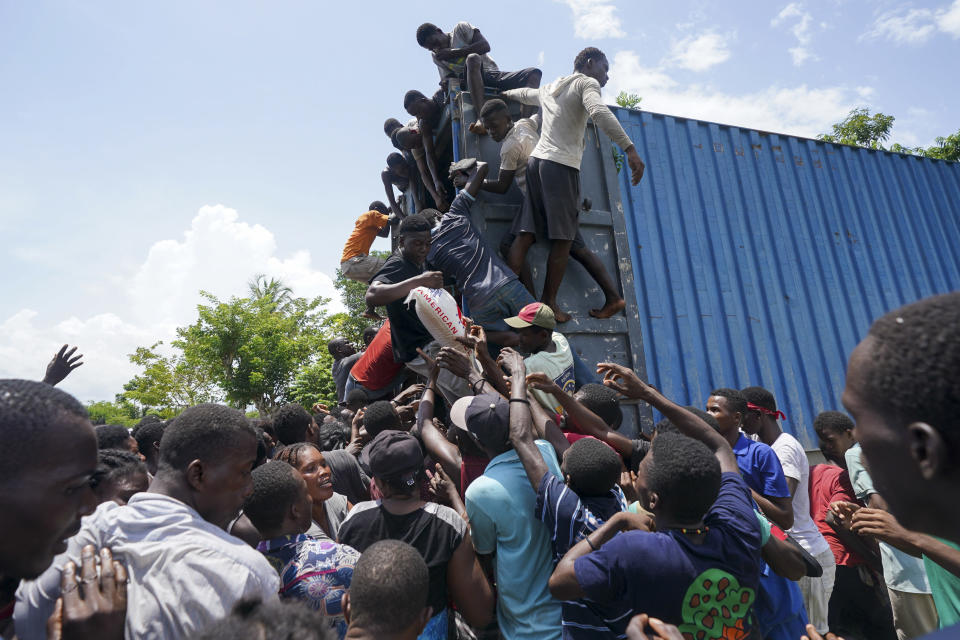 Residents overtake a truck loaded with relief supplies in Vye Terre, Haiti, Friday, Aug. 20, 2021. Private aid and shipments from the U.S. government and others were arriving in the country's southwestern peninsula that was struck by a 7.2 magnitude quake on Aug. 14. (AP Photo/Fernando Llano)
