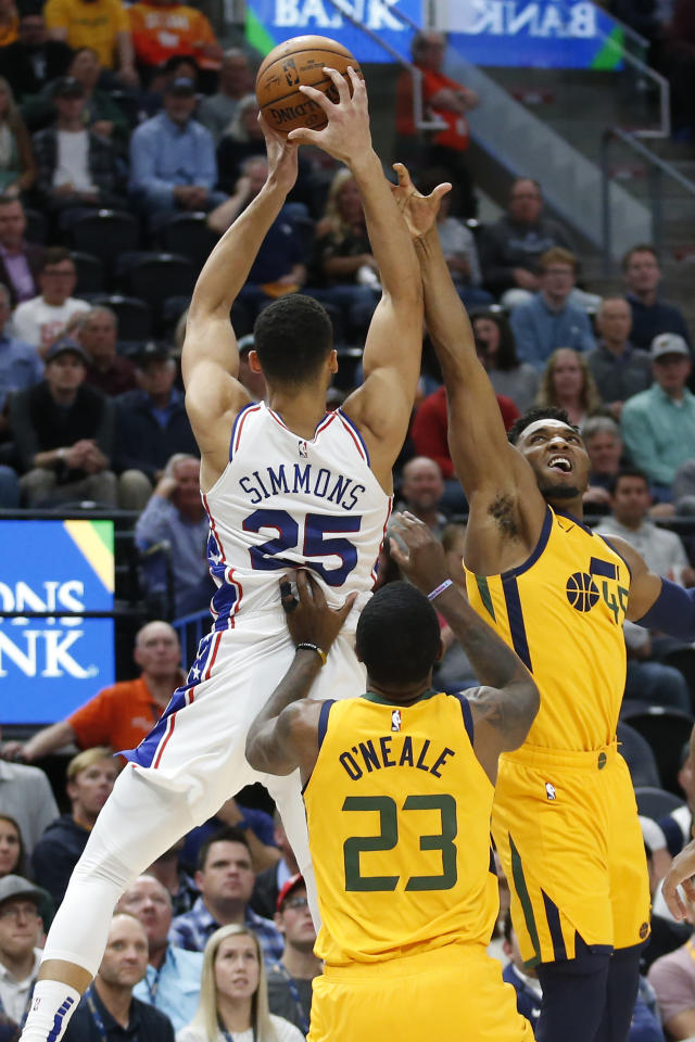 Philadelphia 76ers guard Ben Simmons (25) pulls down a rebound as Utah Jazz's Donovan Mitchell, right, and Royce O'Neale (23) defends in the first half during an NBA basketball game Wednesday, Nov. 6, 2019, in Salt Lake City. (AP Photo/Rick Bowmer)