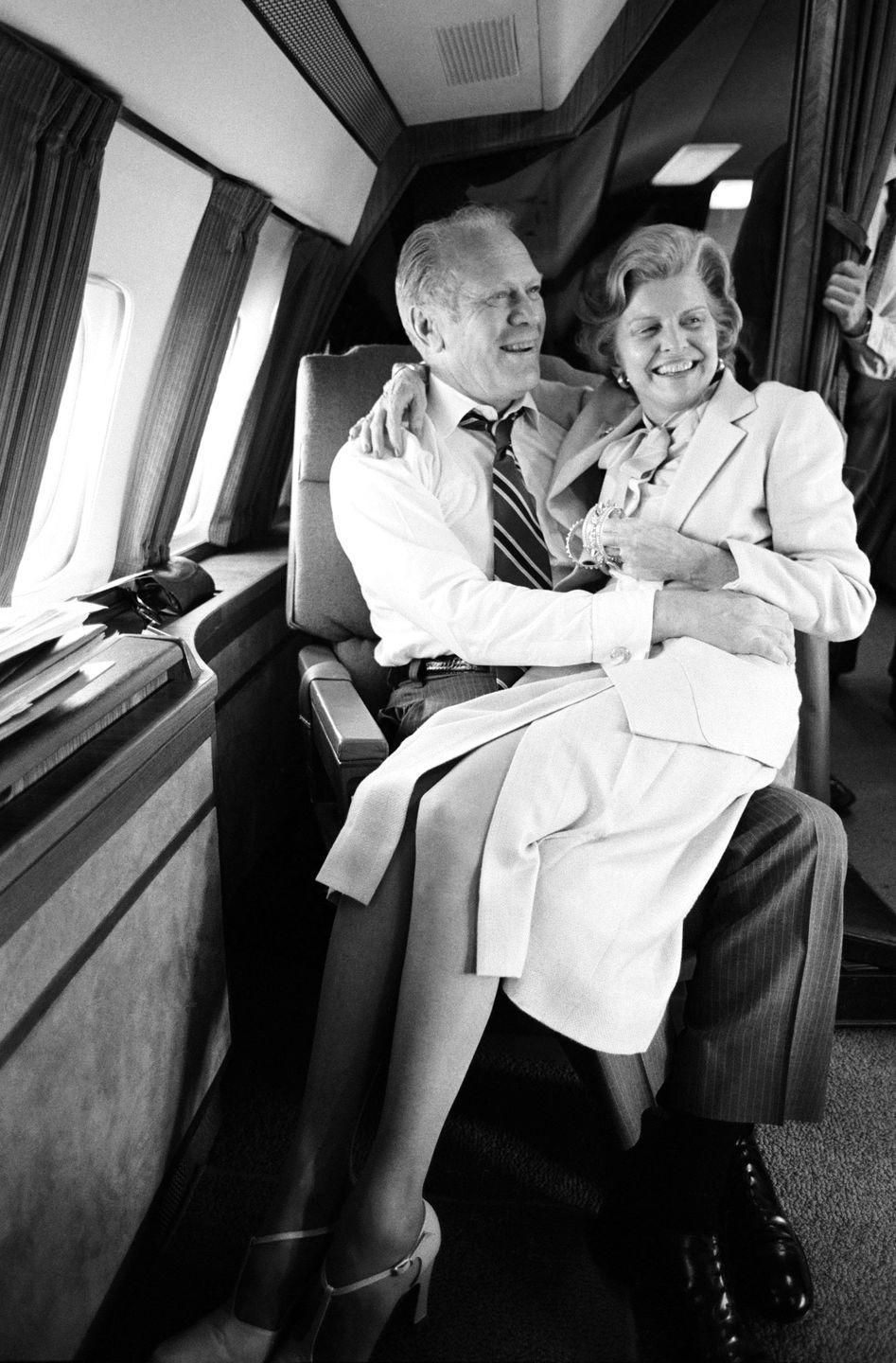 <p>President Gerald R. Ford and his wife Betty Ford share a moment during a flight en route to Oman in 1979. </p>