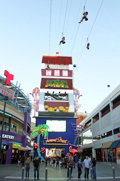 In this April 27, 2014 photo provided by the Fremont Street Experience, guests ride zip lines that swoop past the vintage casinos of downtown Las Vegas and under the giant video canopy of the Fremont Street Experience. The lower zip lines on the $12 million SlotZilla attraction opened over the weekend of April 26 after 14 months of construction. Rides start from a 12-story tower designed like a giant slot machine. Riders can now take the 77-foot-high zip lines, which harness visitors in a sitting position and take them 850 lateral feet to a platform near the 3rd Street Stage. (AP Photo/Fremont Street Experience, Scott Roeben)