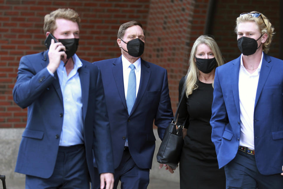 John Wilson, second left, holds his wife's hand, second right, as he leaves the John Joseph Moakley Federal Courthouse after the first day of his trial in the college admissions scandal, Monday, Sept.13, 2021, in Boston. (AP Photo/Stew Milne)