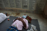 """A patient takes a rest after cataract surgery at an eye camp in Lumbini, 288 kilometers (180 miles) south west of Kathmandu, Nepal, March 31, 2021. Nepal's """"God of Sight"""" eye doctor renowned for his innovative and inexpensive cataract surgery for the poor is taking his work beyond the Himalayan mountains to other parts of the world so there is no more unnecessary blindness in the world. Ruit, who has won many awards for his work and performed some 130,000 cataract surgery in the past three decades, is aiming to expand his work beyond the borders of his home country and the region to go globally. (AP Photo/Bikram Rai)"""