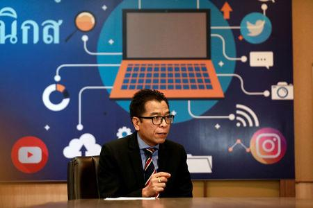 Sawang Boonmee, deputy secretary-general of Election Commission talks as he works in a social media war room in Bangkok