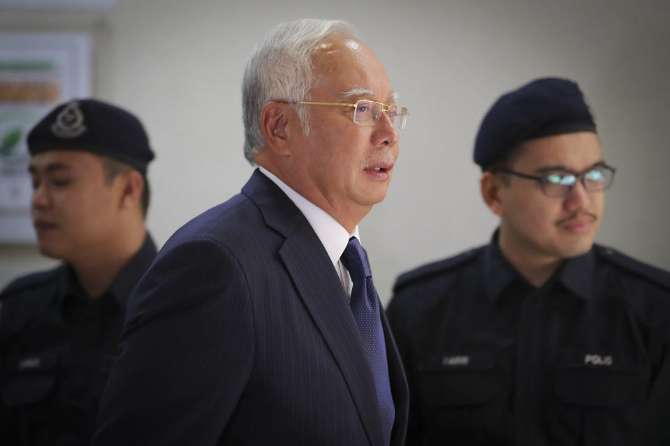 Former Malaysian Prime Minister Najib Razak, center, walks out of a courtroom at Kuala Lumpur High Court in Kuala Lumpur, Malaysia, on Feb. 12, 2019. Najib was found guilty Tuesday, July 28, 2020 in his first corruption trial linked to one of the world's biggest financial scandals - the billion-dollar looting of the 1MDB state investment fund. (AP Photo/Vincent Thian)