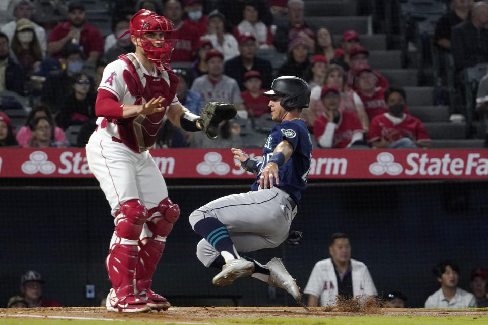 Seattle Mariners' Dylan Moore, right, scores on a single by Ty France as Los Angeles Angels catcher Max Stassi stands at the plate during the third inning of a baseball game Friday, Sept. 24, 2021, in Anaheim, Calif. (AP Photo/Mark J. Terrill)