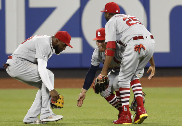 St. Louis Cardinals left fielder Marcell Ozuna, left, center fielder Harrison Bader, center, and right fielder Dexter Fowler celebrate after the Cardinals defeated the New York Mets 9-5 in a baseball game Friday, June 14, 2019, in New York. (AP Photo/Kathy Willens)