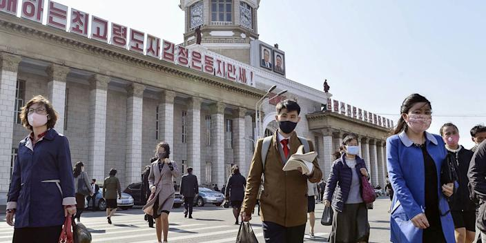 Masked people walk in front of Pyongyang Station on April 27, 2020, amid concerns over the new coronavirus.