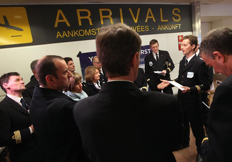 Pilots gather before they distribute leaflets at the arrivals hall of Brussels airport, Tuesday, Jan. 22, 2013. Pilots and cabin crew across Europe held actions against the newly proposed European flight duty time rules which they claim pose a safety risk. (AP Photo/Yves Logghe)