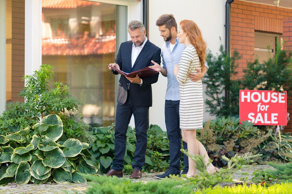 Young couple looking for apartment showing agent which property they want to buy