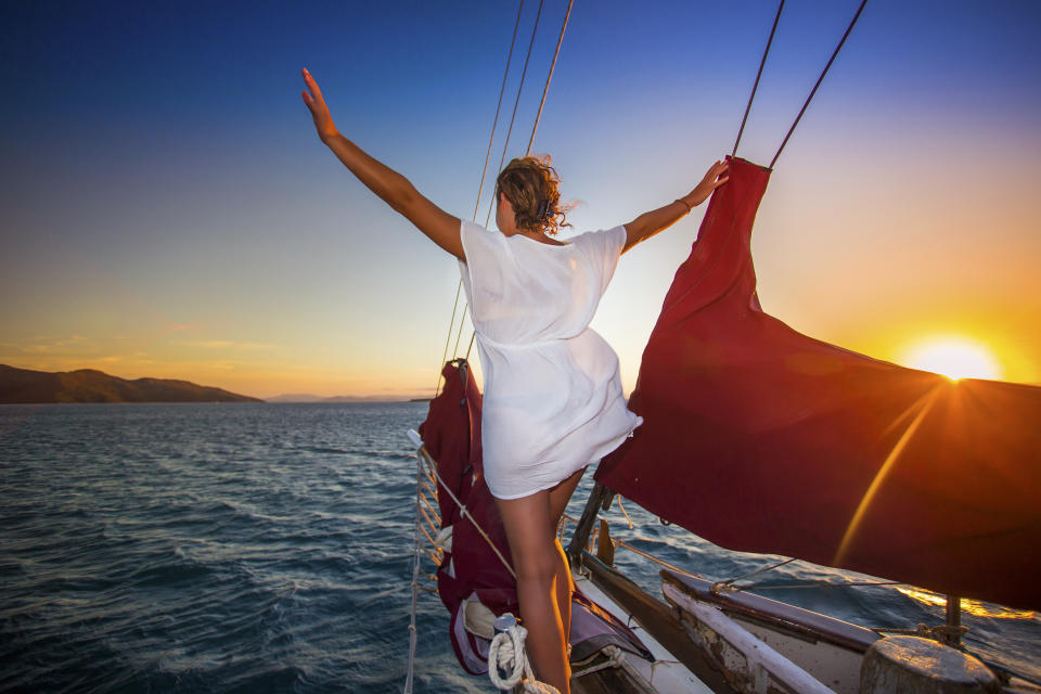Sailing through the Whitsunday Islands is one of the most popular attractions in Australia. Passengers sit and watch the sunset descend over the ocean.