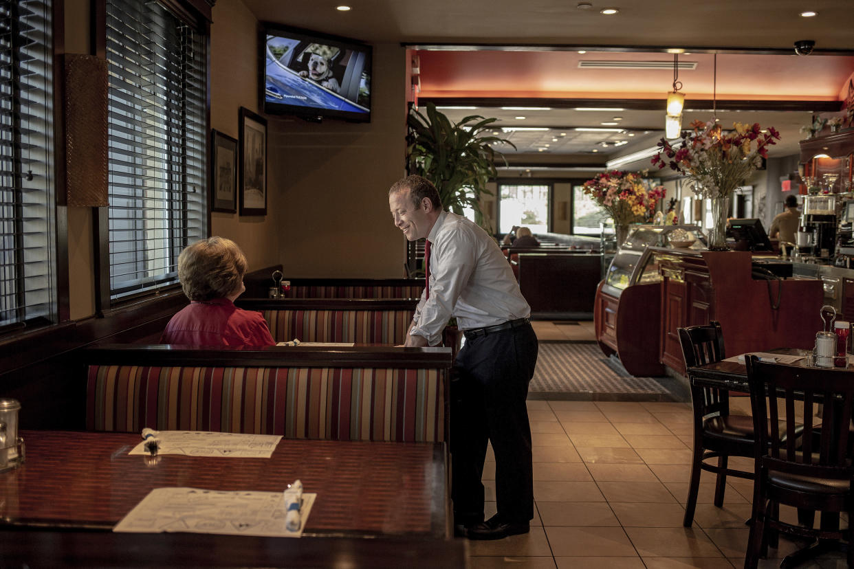 Rep. Josh Gottheimer (D-N.J.) speaks to a server as she takes a break at Tom Sawyer Diner in Paramus, N.J., on Friday, Sept. 27, 2019. (Bryan Anselm/The New York Times)
