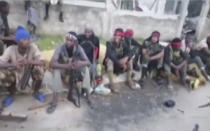In this image taken from militant video released by the Islamic State group on Monday March 29, 2021, purporting to show fighters near the strategic north eastern Mozambique town of Palma, as the militant group claimed it had taken control of the area after five days of conflict. The video from the Islamic State group claims to show fighters in or near Palma, but cannot be independently verified by The Associated Press. (AMAQ Militant video via AP)