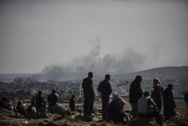 People look at the Syrian town of Kobane from the Turkish border, near the southeastern village of Mursitpinar, October 24, 2014