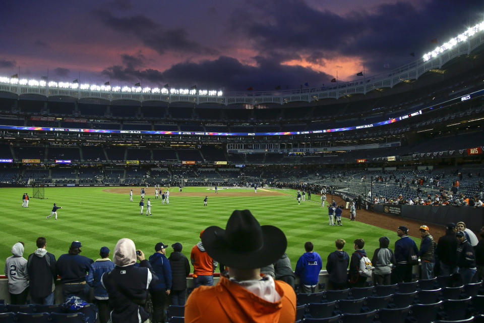 Baseball fans watch batting practice before Game 4 of baseball's American League Championship Series between the New York Yankees and the Houston Astros, Thursday, Oct. 17, 2019, in New York. (AP Photo/Frank Franklin II)