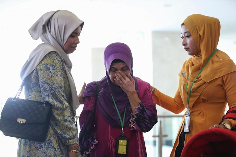 Sarah Nor (C), the mother of Norliakmar Hamid, a passenger on missing Malaysia Airlines flight MH370 at the Ministry of Transport headquarters in Putrajaya, Malaysia (EPA)
