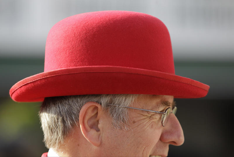 Jim Leuenberger, from Shawano, Wis., wears a red bowler hat white while walking through the paddock before the 138th Kentucky Derby horse race at Churchill Downs, Saturday, May 5, 2012, in Louisville, Ky. The Run for the Roses draws them to Churchill Downs. But what race goers wear is as much a spectacle in itself. (AP Photo/Mark Humphrey)