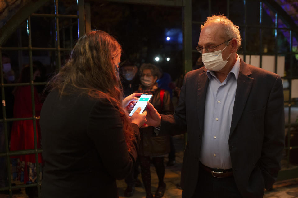 "A man presents his ""green passport,"" proof that he is vaccinated against the coronavirus, on opening night at the Khan Theater for a performance where all guests were required to show proof of vaccination or full recovery from the virus, in Jerusalem, Tuesday, Feb. 23, 2021. (AP Photo/Maya Alleruzzo)"