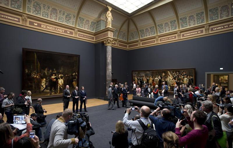 Journalists take pictures and video footage as dignitaries including museum director Wim Pijbes, center, pose in front of Dutch master Rembrandt's The Night Watch painting during a press preview of the renovated Rijkmuseum in Amsterdam, Thursday, April 4, 2013. The Rijksmuseum, home of Rembrandt's Night Watch and other national treasures, is preparing to reopen its doors on April 13 2013 after a decade-long renovation. (AP Photo/Peter Dejong)