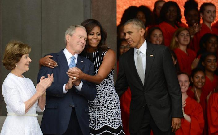 President Barack Obama watches first lady Michelle Obama embracing former president George Bush, accompanied by his wife, former first lady Laura Bush, while participating in the dedication of the National Museum of African American History and Culture September 24, 2016 in Washington, DC, before the museum opens to the public later that day. The museum is a Smithsonian Institution museum located on the National Mall featuring African American history and culture in the US. (Photo by Astrid Riecken/Getty Images)
