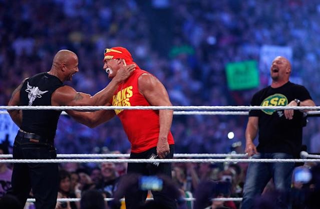 "IMAGE DISTRIBUTED FOR WWE - Dwayne Johnson aka The Rock, left, embraces Hulk Hogan, center, as ""Stone Cold"" Steve Austin looks on during Wrestlemania XXX at the Mercedes-Benz Super Dome in New Orleans on Sunday, April 6, 2014. (Jonathan Bachman/AP Images for WWE)"
