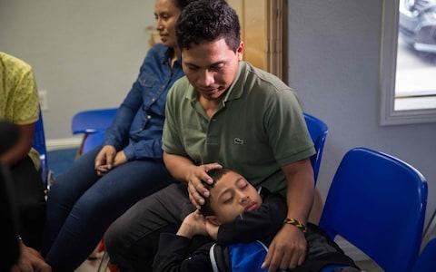 An immigrant from El Salvador and his 10-year-old son rest after being released from detention in McAllen, Texas - Credit:  LOREN ELLIOTT/AFP