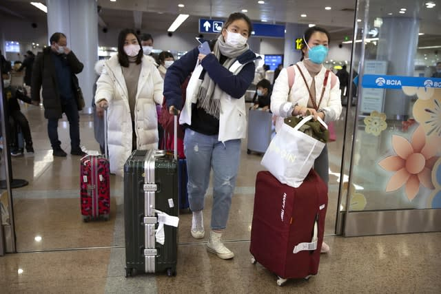 Travellers wearing face masks enter the arrivals area at Beijing Capital International Airport (Mark Schiefelbein/AP)