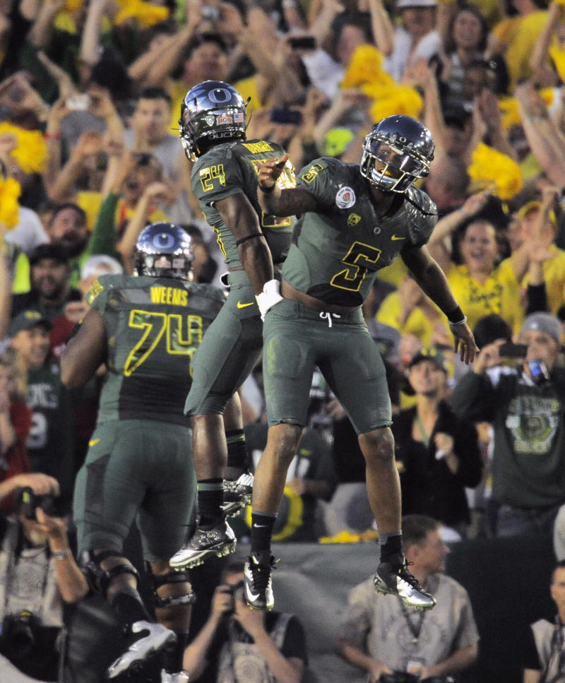 Oregon quarterback Darron Thomas (5) celebrates with Kenjon Barner (24) after throwing a touchdown pass during the second half of the Rose Bowl NCAA college football game against Wisconsin, Monday, Jan. 2, 2012, in Pasadena, Calif.  (AP Photo/Mark J. Terrill)