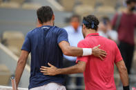 Switzerland's Roger Federer, right, gives Croatia's Marin Cilic a pat on the back as they meet at the net after Federer defeated him in their second round match on day 5, of the French Open tennis tournament at Roland Garros in Paris, France, Thursday, June 3, 2021. (AP Photo/Michel Euler)