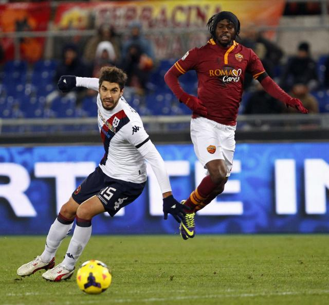 AS Roma's Gervinho and Cagliari's Luca Rossettini (L) fight for the ball during their Italian Serie A soccer match at the Olympic stadium in Rome November 25, 2013. REUTERS/Giampiero Sposito (ITALY - Tags: SPORT SOCCER)