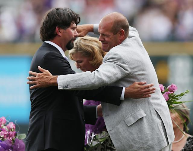 Retired Colorado Rockies first baseman Todd Helton, left, is hugged by the team's co-owner Charlie Monfort during a ceremony to retire Helton's jersey number before the Rockies host the Cincinnati Reds in a baseball game in Denver on Sunday, Aug. 17, 2014. (AP Photo/David Zalubowski)