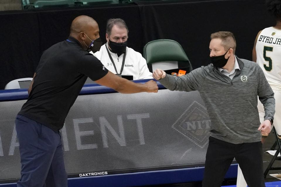 Memphis head coach Penny Hardaway, left, and Colorado State head coach Niko Medved, right, greet each other after their NCAA college basketball game in the semifinals of the NIT, Saturday, March 27, 2021, in Frisco, Texas. (AP Photo/Tony Gutierrez)