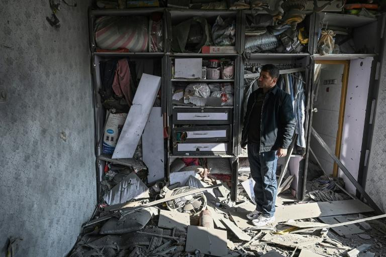 In Afghanistan, a man inspects a damaged house after several rockets landed on Saturday, that latest in a string of attacks