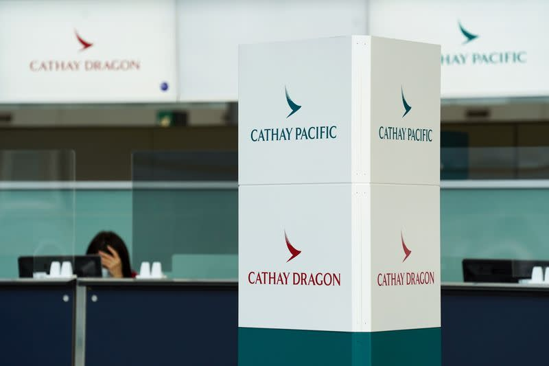 Cathay Pacific and Cathay Dragon logos are seen near a counter at Hong Kong International Airport