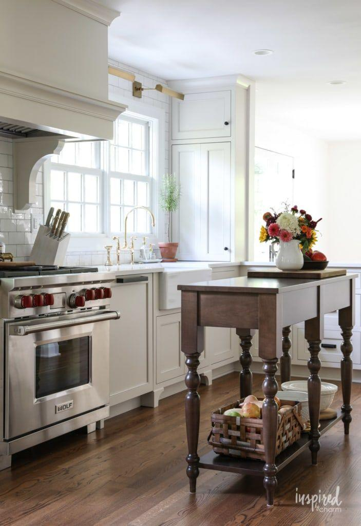 """<p>The final result is a chic all-white kitchen, complemented by dark wood floors and an antique table standing in for a kitchen island.</p><p><strong>Get the tutorial at <a href=""""https://inspiredbycharm.com/bayberry-kitchen-remodel-reveal/"""" rel=""""nofollow noopener"""" target=""""_blank"""" data-ylk=""""slk:Inspired by Charm"""" class=""""link rapid-noclick-resp"""">Inspired by Charm</a>.</strong></p><p><strong><a class=""""link rapid-noclick-resp"""" href=""""https://www.amazon.com/OWOFAN-16-Inch-Commercial-Function-Polished/dp/B07TB3VHQV/?tag=syn-yahoo-20&ascsubtag=%5Bartid%7C2139.g.34085615%5Bsrc%7Cyahoo-us"""" rel=""""nofollow noopener"""" target=""""_blank"""" data-ylk=""""slk:SHOP KITCHEN FAUCETS"""">SHOP KITCHEN FAUCETS</a><br></strong></p>"""