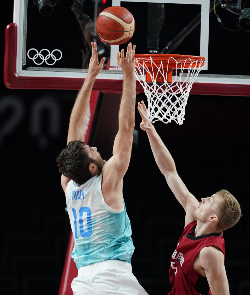 Slovenia's Mike Tobey (10), left, shoots over Germany, right, during men's basketball quarterfinal game at the 2020 Summer Olympics, Tuesday, Aug. 3, 2021, in Saitama, Japan. (AP Photo/Charlie Neibergall)