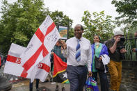 Anthony Brown, director of the Windrush Defenders C.I.C. marches holding an England's flag, as he takes part in the annual Afrikan Emancipation Day Reparations march, in Brixton, London, Sunday, Aug. 1, 2021. Black people whose right to live in the U.K. was illegally challenged by the government marked the anniversary Sunday of the act that freed slaves throughout the British Empire, drawing a direct link between slavery and the discrimination they suffered. Dozens of campaigners gathered in Brixton, a center of the Black community in south London, to back the international drive for reparations for the descendants of enslaved Africans and demand legislation to compensate legal residents who were threatened with deportation in what is known as the Windrush Scandal. (AP Photo/Alberto Pezzali)