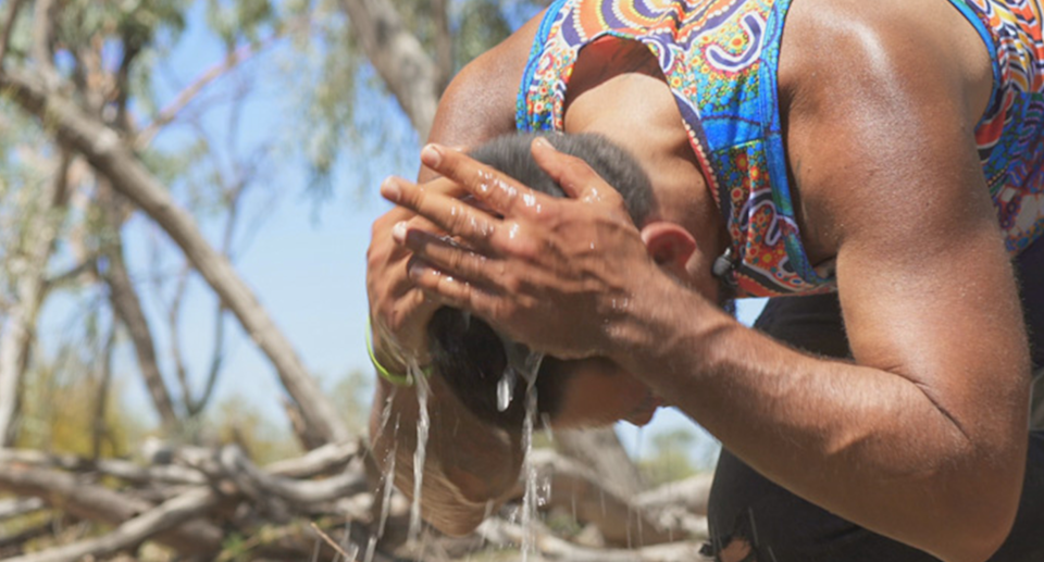 An Indigenous man washing his hair with the water from Doongmabulla Springs.