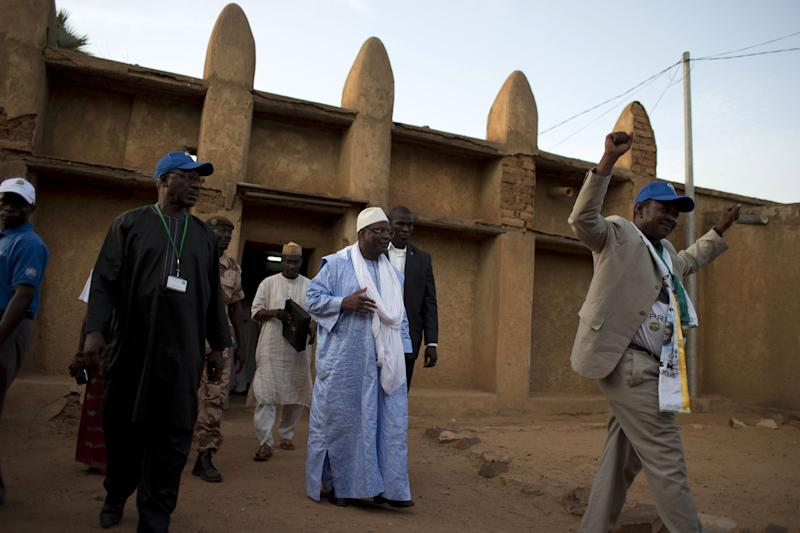 A local government official, right, cheers as presidential candidate Ibrahim Boubacar Keita, center, known by his initials 'IBK,' emerges from a mosque after meeting with an imam in Bandiagara, Dogon Country, Mali, Sunday, July 21, 2013. Candidates are traveling the country holding rallies as they head into the final week of campaigning ahead of Mali's July 28 presidential vote. (AP Photo/Rebecca Blackwell)