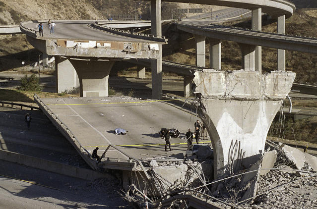 FILE - In this Jan. 17, 1994, file photo, the covered body of Los Angeles Police Officer Clarence Wayne Dean lies near his motorcycle which plunged off the State Highway 14 overpass that collapsed onto Interstate 5, after a magnitude-6.7 Northridge earthquake in Los Angeles. Twenty-five years ago this week, a violent, pre-dawn earthquake shook Los Angeles from its sleep, and sunrise revealed widespread devastation, with dozens killed and $25 billion in damage. (AP Photo/Doug Pizac, File)