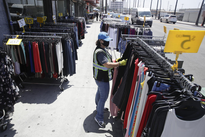A woman shops for clothes Wednesday, May 27, 2020, in Los Angeles. California moved to further relax its coronavirus restrictions and help the battered economy. Retail stores, including those at shopping malls, can open at 50% capacity. (AP Photo/Marcio Jose Sanchez)